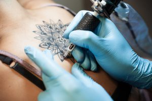 Tattoo artist at work on a girl's backpiece