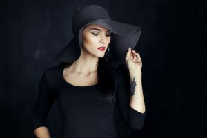 Beautiful brunette woman looking away, wearing a hat.